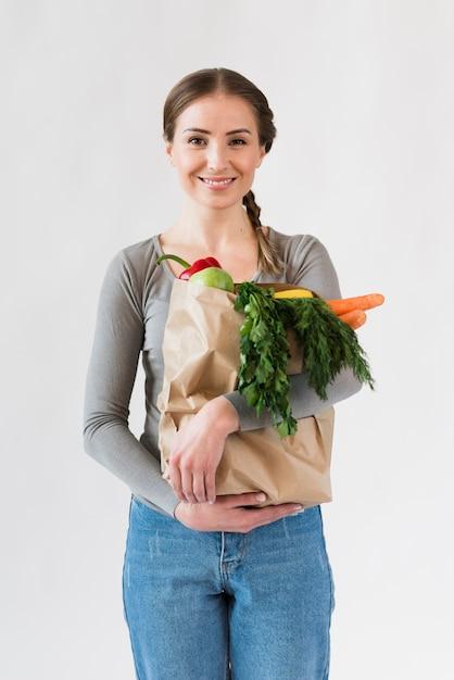 Retrato de mujer joven con bolsa de papel con comestibles Foto gratis