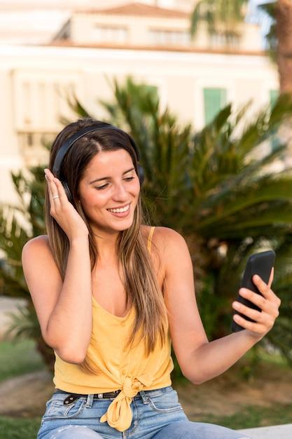Retrato de mujer joven y bonita escuchando música Foto gratis