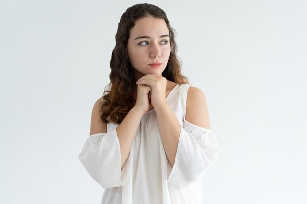 Retrato de mujer joven concentrada de pie con las manos juntas Foto gratis