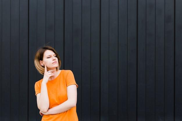 Retrato de una mujer joven contemplada de pie contra la pared negra Foto gratis
