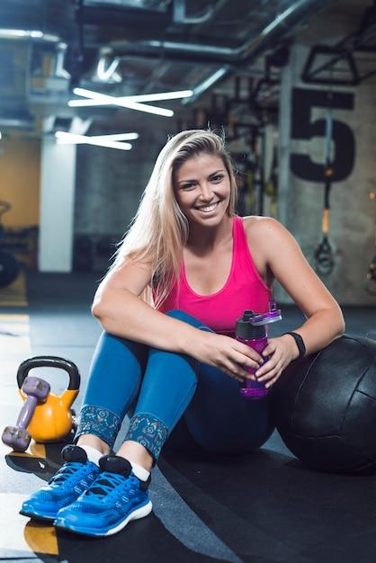 Retrato de una mujer joven feliz con botella de agua Foto gratis