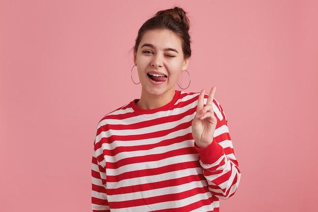 Retrato de una mujer joven feliz con pecas, viste manga larga a rayas, guiños, mostrando gesto de paz y sacando la lengua aislada sobre pared rosa. Foto gratis