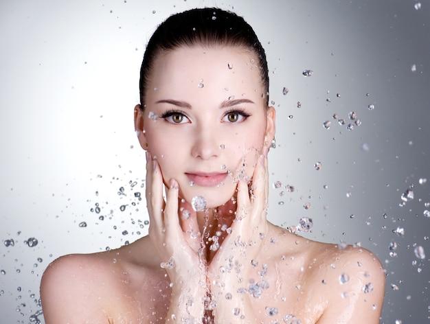 Retrato de mujer joven hermosa con gotas de agua alrededor de su rostro Foto gratis