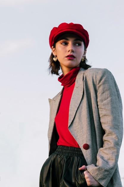 Retrato de una mujer joven hermosa que se coloca delante del cielo azul Foto gratis