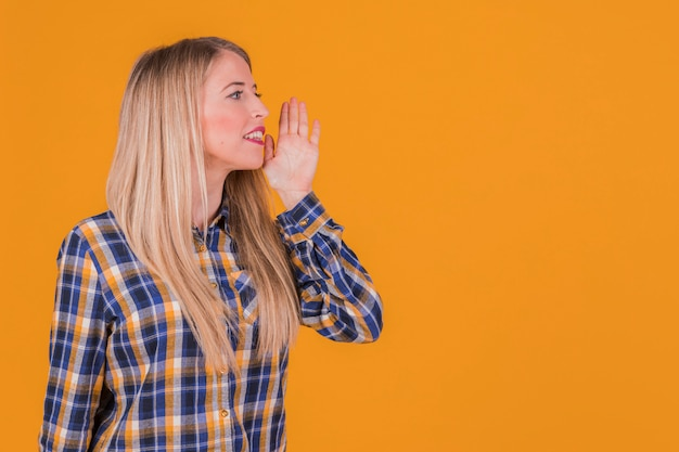 Retrato de una mujer joven llamando a alguien en un contexto naranja Foto gratis