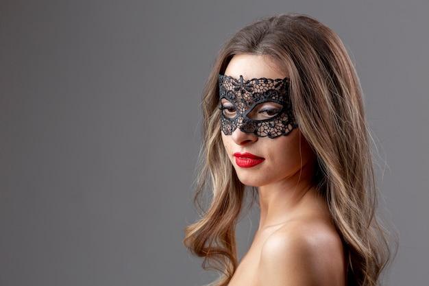 Retrato de mujer joven con máscara de carnaval Foto gratis