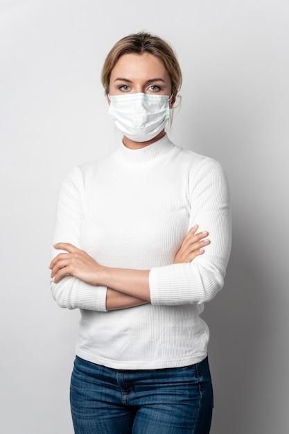 Retrato de mujer joven con máscara quirúrgica posando Foto gratis