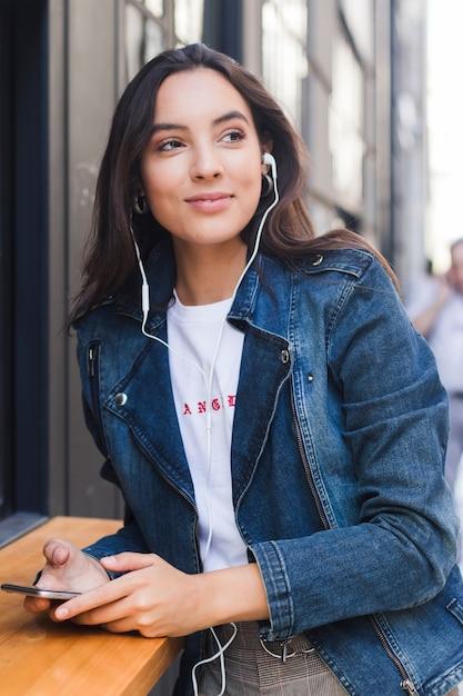 Retrato de una mujer joven en música que escucha de la chaqueta azul del dril de algodón en el auricular a través del teléfono móvil Foto gratis