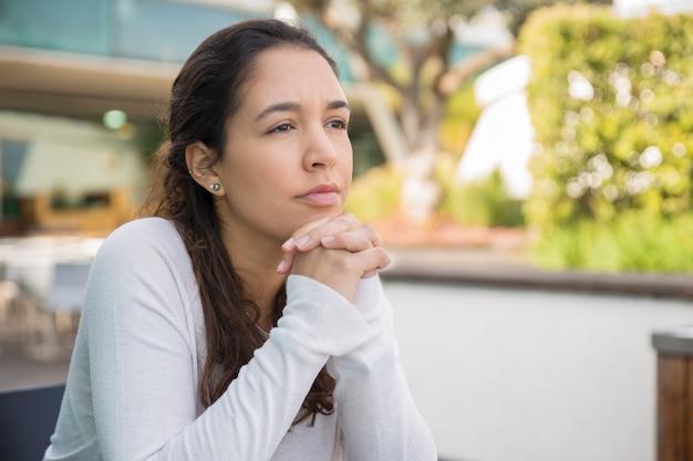 Retrato de mujer joven pensativa o triste que se sienta en el café de la acera Foto gratis