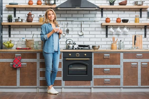 Retrato de una mujer joven de pie cerca del mostrador de la cocina con una taza de café en la mano Foto gratis