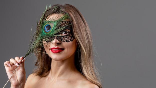 Retrato de mujer joven con plumas de pavo real Foto gratis