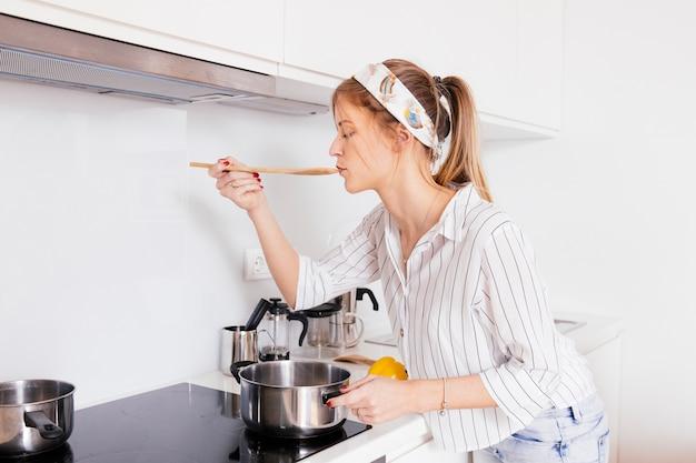 Retrato de una mujer joven probando la sopa mientras se prepara en la cocina Foto gratis