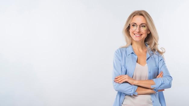 Retrato de la mujer joven que se coloca con sus brazos cruzados contra el fondo blanco Foto gratis