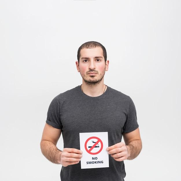 Retrato de una mujer joven que lleva a cabo la muestra de no fumadores contra el fondo blanco Foto gratis