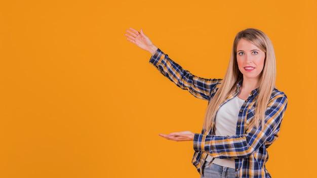 Retrato de una mujer joven que presenta algo sobre un fondo naranja Foto gratis