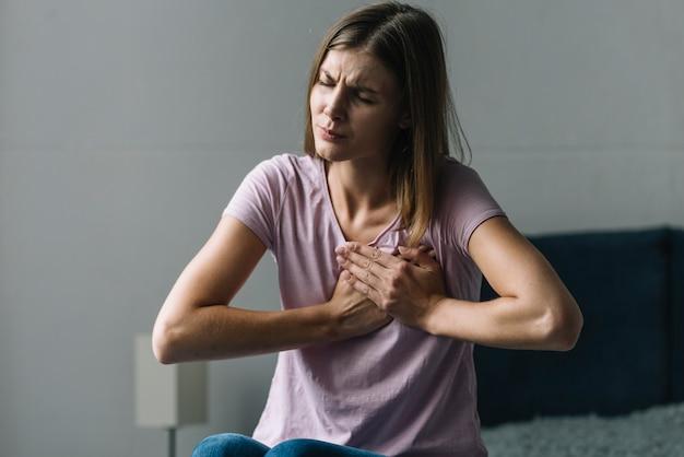 Retrato de una mujer joven que sufre de dolor en el pecho..