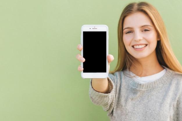 f33cf6da4d12 Retrato de una mujer joven rubia feliz que muestra el teléfono móvil ...