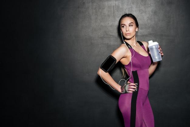 Retrato de una mujer joven y saludable fitness sosteniendo la botella de agua Foto Premium