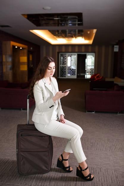 Retrato mujer joven sentada en maletas en la terminal o estación de tren, la mujer se reunió en un viaje. Foto Premium