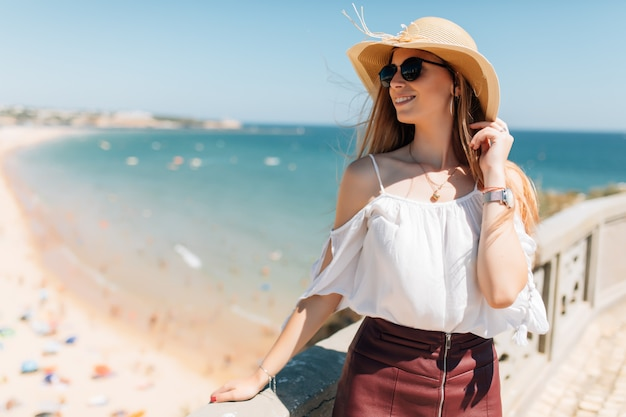 Retrato de mujer joven con sombrero y gafas de sol redondas, clima ventoso agradable día de verano en el océano Foto gratis