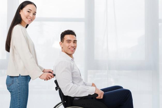 Retrato de una mujer joven sonriente que se coloca detrás del hombre que se sienta en la silla de rueda que mira la cámara Foto gratis
