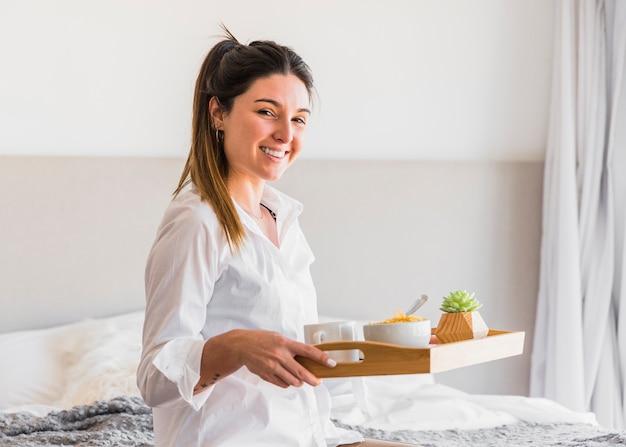 Retrato de una mujer joven sonriente que sostiene la bandeja del desayuno Foto gratis