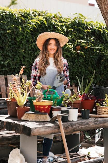 Retrato de una mujer joven sonriente que sostiene los guantes que cultivan un huerto que se colocan detrás de las plantas en la tabla Foto gratis