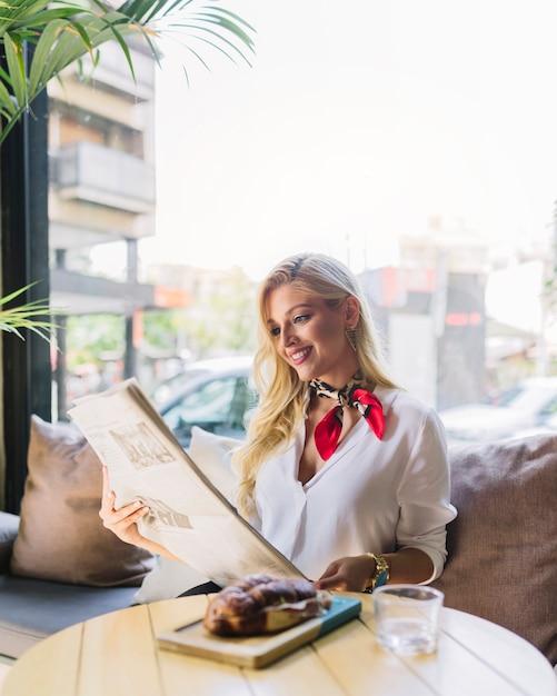 Retrato de una mujer joven sonriente sentada en el café leyendo el periódico Foto gratis