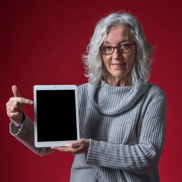 Retrato de una mujer mayor que señala su dedo en la tableta digital contra fondo coloreado Foto gratis