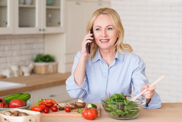 Retrato de una mujer mayor rubia sonriente que habla en el teléfono móvil que prepara la ensalada verde Foto gratis