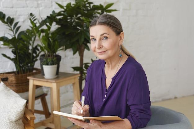 Retrato de una mujer de mediana edad moderna y ocupada de 50 años con camisa violeta escribiendo en un cuaderno, haciendo planes, mirando con una sonrisa amistosa positiva, sentado en una silla, rodeado de plantas verdes Foto gratis