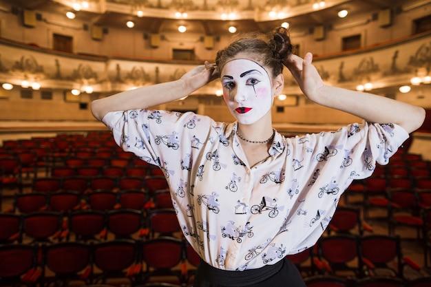 Retrato de mujer mimo de pie en un auditorio Foto gratis