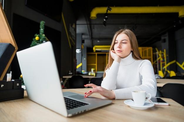 Retrato de mujer moderna trabajando con portátil Foto gratis