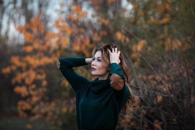 El retrato de la mujer morena joven atractiva con el pelo fijó en suéter verde del otoño y la falda larga que presentaba en el parque del otoño. copia espacio Foto Premium