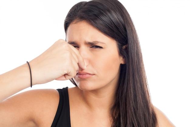 Retrato de una mujer morena que se pellizca la nariz debido a un mal olor Foto Premium