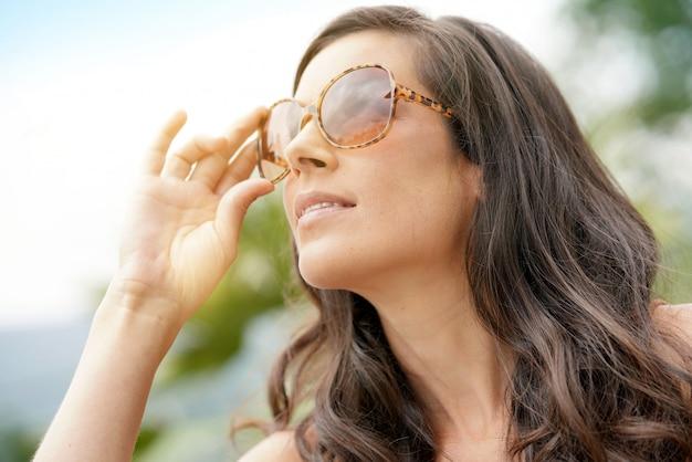 ed2f296163 Retrato de la mujer morena sonriente que lleva las gafas de sol   Descargar  Fotos premium