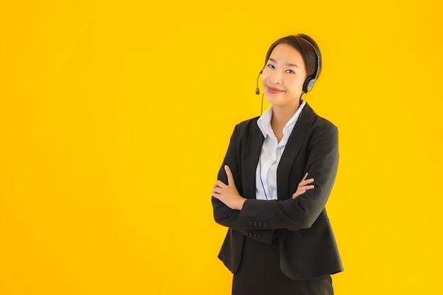 Retrato mujer de negocios asiática joven hermosa con auriculares o auriculares Foto gratis