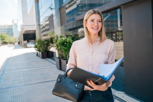 Retrato de mujer de negocios joven sosteniendo el portapapeles mientras está parado al aire libre en la calle. concepto de negocio. Foto gratis