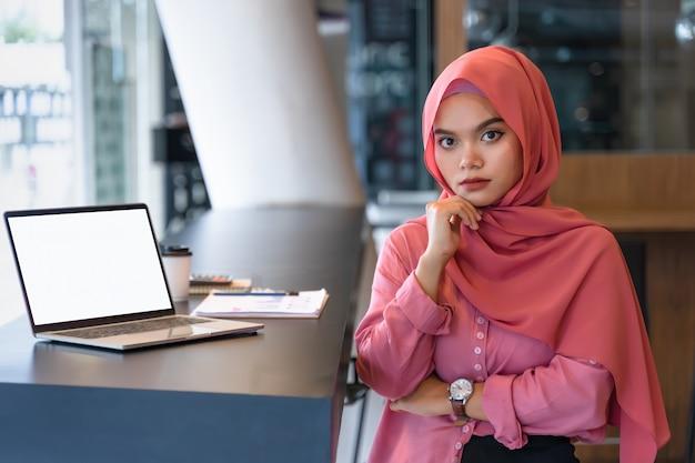 Retrato de la mujer de negocios musulmán joven confiada que lleva el hijab rosado en el espacio del trabajo conjunto. Foto Premium