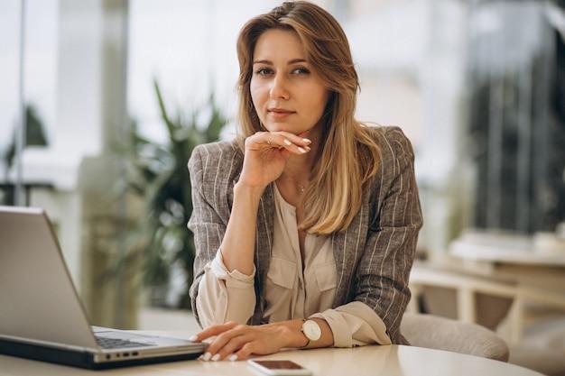 Retrato de una mujer de negocios trabajando en la computadora portátil Foto gratis