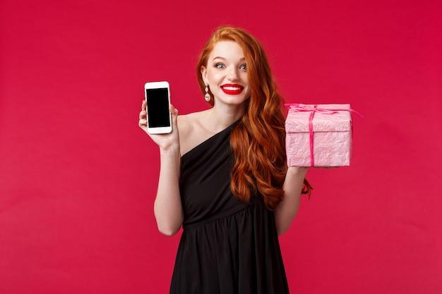 Retrato de una mujer pelirroja sonriente, emocionada y divertida, preguntada, no se expandió, recibió el regalo tan rápido, mostrando la aplicación de teléfono móvil, la aplicación de entrega en línea, sostenga el presente rosa sobre la pared roja Foto Premium