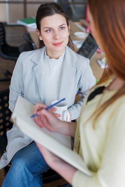 Retrato de la mujer que se sienta en la silla que sostiene la taza de café que mira a su colega Foto gratis