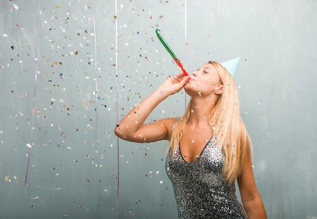 Retrato de la mujer rubia elegante joven que celebra un partido. Foto Premium
