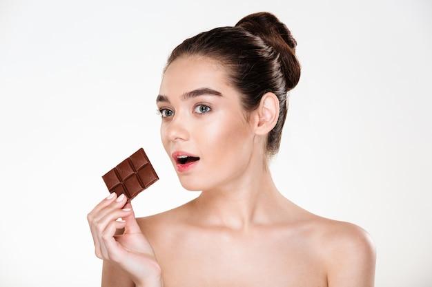 Retrato de mujer semidesnuda hambrienta con cabello oscuro comiendo chocolate bar no está a dieta Foto gratis