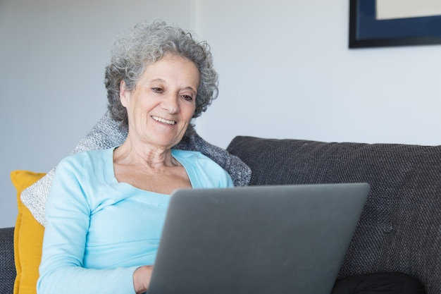 Retrato de mujer senior feliz usando laptop en casa Foto gratis