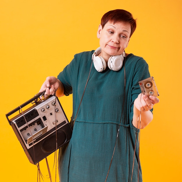 Retrato de mujer senior con reproductor de cassette Foto gratis
