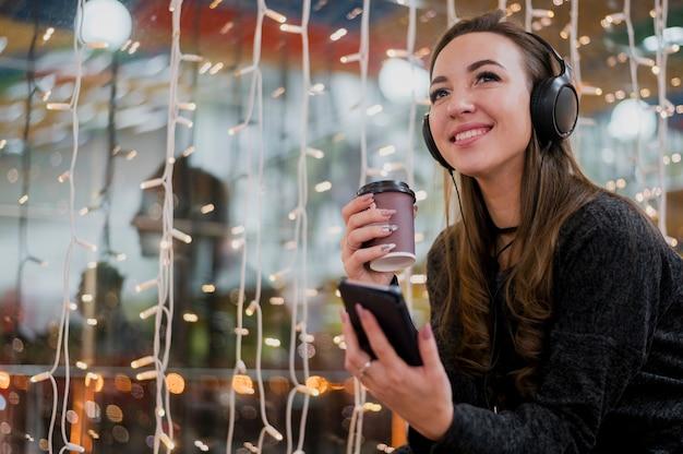 Retrato de mujer sonriente con auriculares con taza y teléfono cerca de luces de navidad Foto gratis