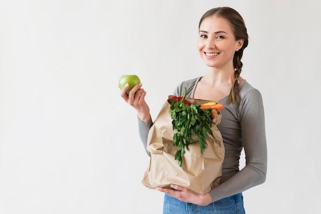 Retrato de mujer sonriente con bolsa con frutas y verduras Foto gratis