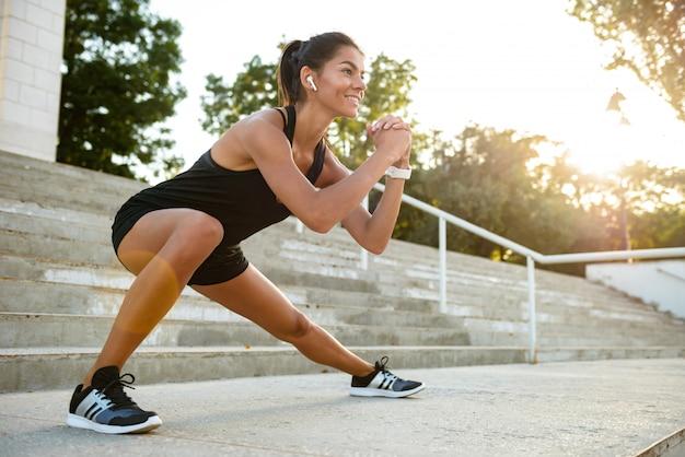 Retrato de una mujer sonriente de fitness en auriculares Foto gratis