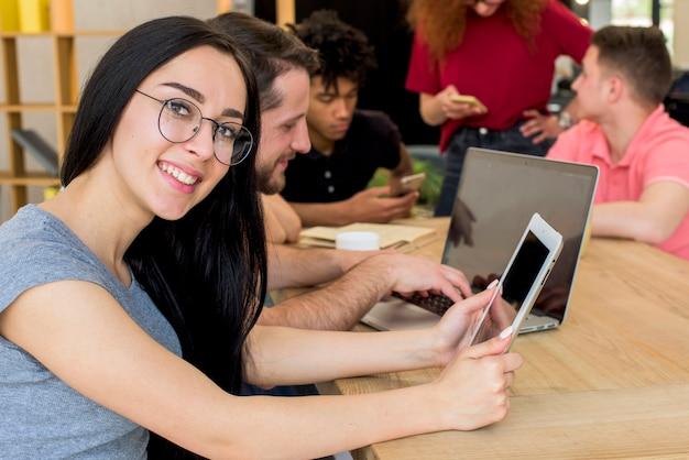 Retrato de la mujer sonriente que sostiene la tableta digital que mira la cámara mientras que se sienta al lado de sus amigos que usan los artilugios y el libro electrónicos en el escritorio de madera Foto gratis